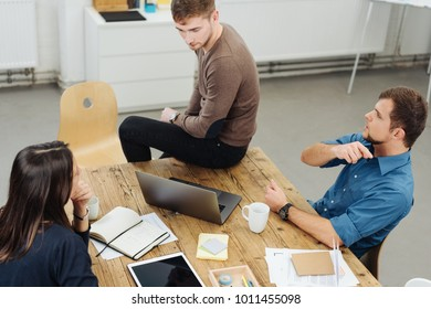 Three businesspeople having a meeting together in a high angle view of them grouped around an office table talking with paperwork and tablet-pc