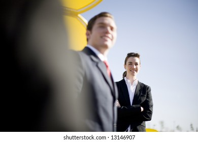 three businesspeople in a row with businesswoman standing looking at the camera with her arms crossed