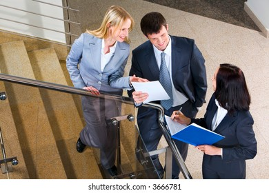 Three businesspeople run across on the stairs of the business building showing documents to each other and making notes