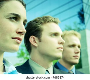 three businesspeople standing facing  same direction