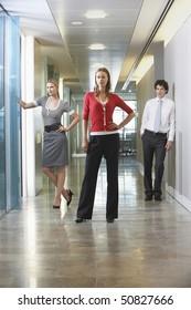 Three businesspeople standing in office corridor, portrait