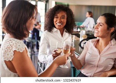 Three Businesswoman Meeting For After Works Drinks In Bar Making A Toast