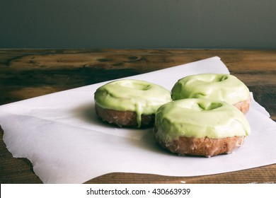 Three cake donuts with matcha icing. Low key.