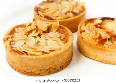 Three cakes with almond on the top, isolated on white plate