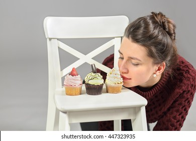 Three cakes stand on white chair, young girl bent over cake on his knees