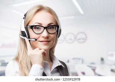 Three call center service operators at work. Portrait of smiling pretty female helpdesk employee with headset at workplace.