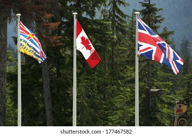 Three Canadian Flags. British Columbia, Canada National and British National Flag. Tree Large Flags on Poles.