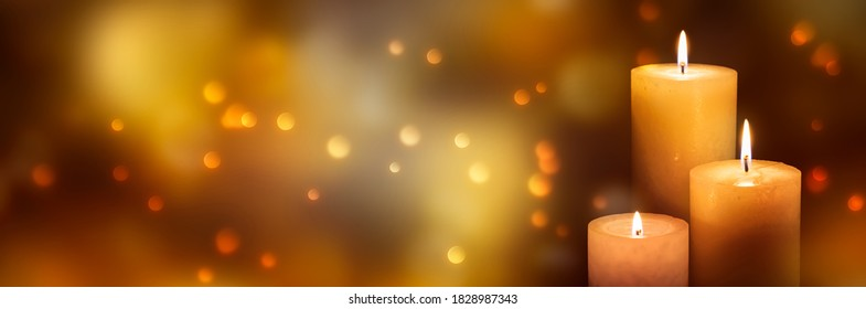 three candle lights at the edge of blurred festive background, decorative golden shiny candle lights
