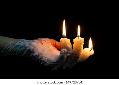 Three candle sticks on fingers burning with wax flow