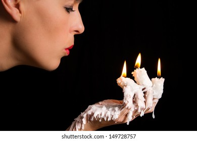 Three candle sticks on fingers burning with wax flow face blowing