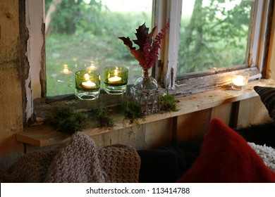 Three candles and autumn leaves on windowsill of a country house