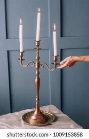three candles in a candelabra on a table in retro style