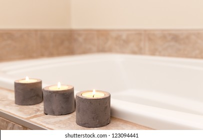 Three candles in concrete candle holders decorating bathroom.