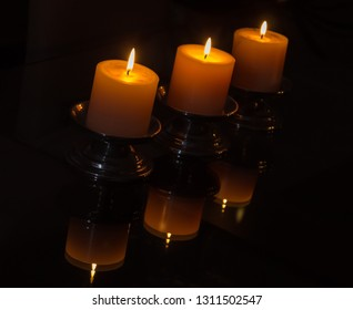 Three candles lighted, darkness, pewter base