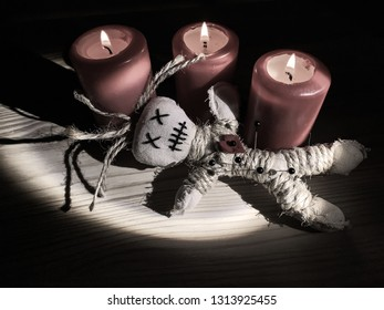 Three candles and a voodoo doll are on a table