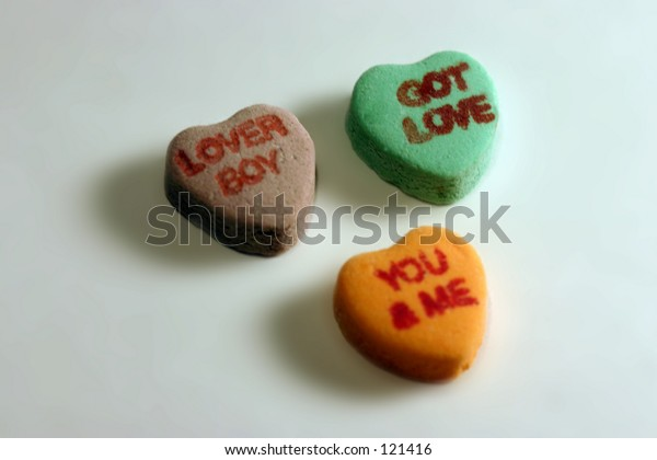 Three candy hearts with writing.