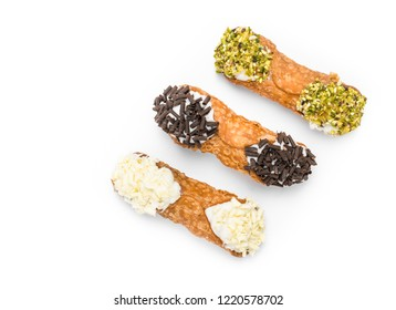 Three cannoli pastries. Traditional Sicilian dessert, filled with a rich ricotta cream  enriched with pistachio grain, hazelnut grain and chocolate flakes.
