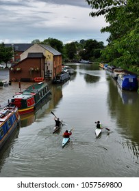 Three canoes on a canal in Wiltshire, England on a rainy morning.