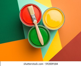three cans  yellow green and red paint and brush on colourful geometrical background