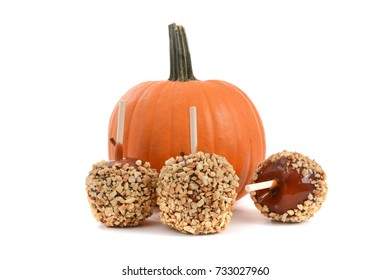 three caramel apples and a pumpkin isolated on a white background