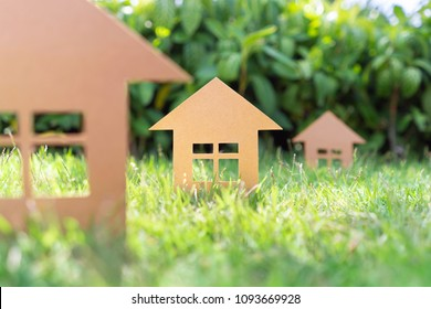 Three carboard houses on a grass lawn sun trees