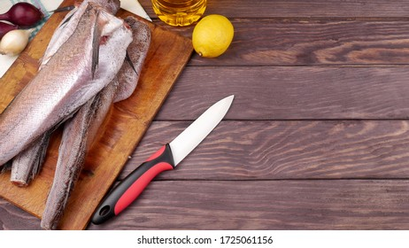 Three carcasses of fresh-frozen hake, pollock fish, on a cutting board on a wooden table. In the background is a knife, lemon, onion and a bottle of sunflower oil. Place for text.