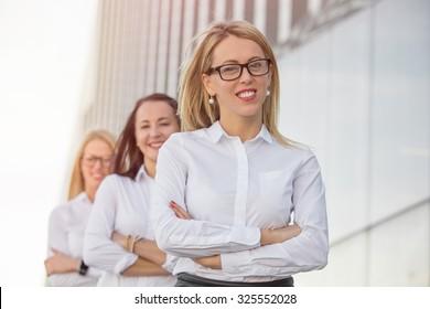 Three career women standing with crossed hands