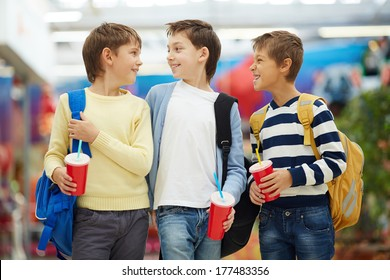 Three carefree schoolboys talking after studies