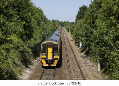 A three carriage train running on the line between Salisbury and Exeter England. Image taken from a footbridge, looking towards the oncoming train with double tracks to vanishing point.