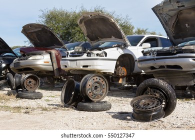 three cars and wheel displays to attract attention in a salvage yard