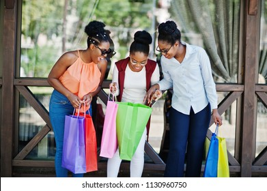 Three casual african american girls with colored shopping bags walking outdoor. Stylish black womans shopping.