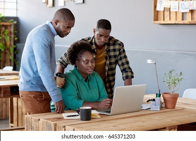 Three casually dressed young African office colleagues using a laptop while working together at a table in a modern office