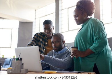 Three casually dressed young African businesspeople talking together and using a laptop while working at a table in a modern office