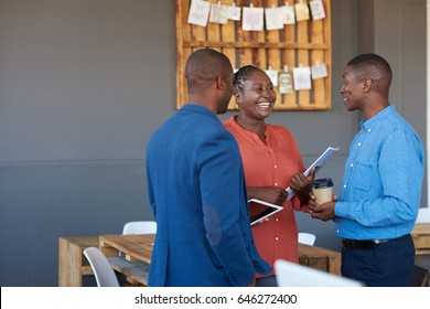 Three casually dressed young African office coworkers smiling and talking together while standing in a large modern office