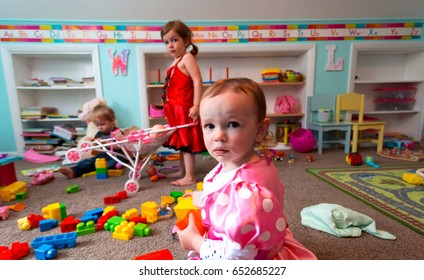 Three Caucasian Children Play Together In Their Suburban Home Play Room