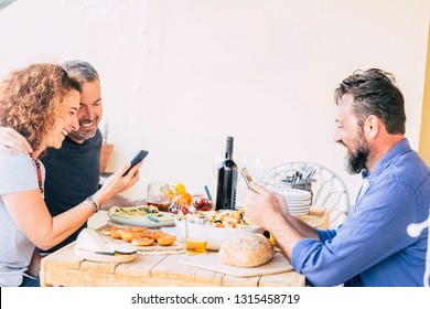 Three caucasian friends eating at the restaurant each one looking the phone and not speaking with the others - internte cellular addicted people - bad use of technology concept