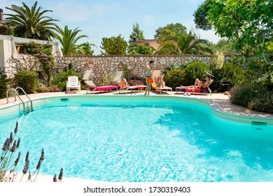 Three Caucasian men sunbathing beside the swimming pool