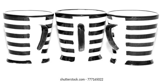 Three ceramic mugs striped black and white with black handles taken against white background.