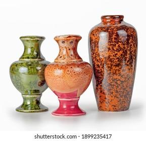 Drei Keramikvasen in grüner und brauner Farbe, einzeln auf weißem Hintergrund in einer Reihe angeordnet.