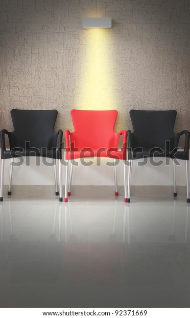 Three chairs in line and light on the middle chair. Concept of being different from the rest.