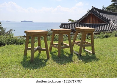 Three chairs in a scenery with a view of the sea behind the Korean tile building