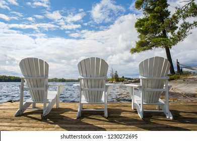 Three chairs sitting on a wood dock facing a calm lake. A hammock is partially visible.