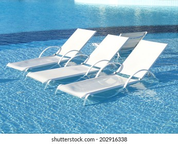 swimming pool lounge chair. Chaise Lounges In Swimming Pool. Three Longue At The Poolside Pool Lounge Chair