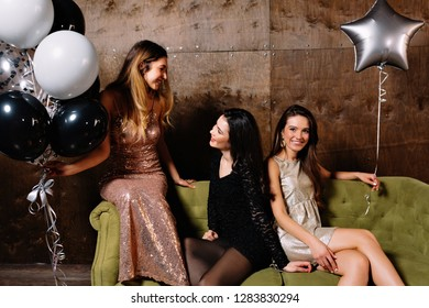 Three charming attractive women celebrating a party, dancing, talking to eath other, with balloons. Indoor photo of funny ladies chilling at home during christmas celebration and drinking champagne.