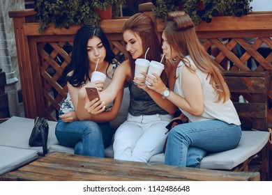 three charming girls sitting at the table on the terrace of the cafe and drinking coffee