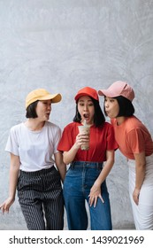 Three cheerful asian female teenager friends enjoying with bubble milk tea against grey concrete background