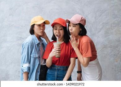 Drei fröhliche asiatische Teenagerfreunde, die sich mit einem Milchtee aus Blase auf grauem Beton freuen
