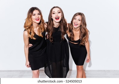Three cheerful charming young women in black dresses standing and laughing over white background
