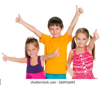 Three cheerful children holding their thumbs up on the white background