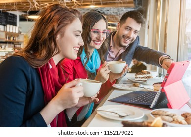 Three cheerful colleagues watching together a funny video on laptop during coffee break in a trendy coffee shop